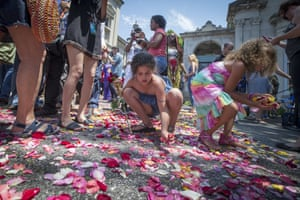 Children and spectators collect petals from the road that Muhammad Ali's funeral procession passed along