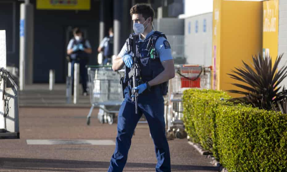 An armed police officer patrols outside the supermarket where an extremist stabbed several shoopers in Auckland, New Zealand.