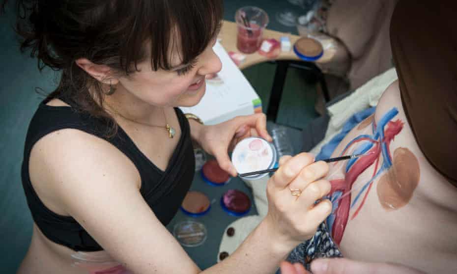 Trainee plastic surgeon Meg Anderson paints internal organs on body