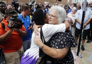 Susan Bro, mother of Heather Heyer, who was killed during last year's Unite the Right rally, embraces supporters after laying flowers at the spot her daughter was killed in Charlottesville, Virginia, in August 2018.