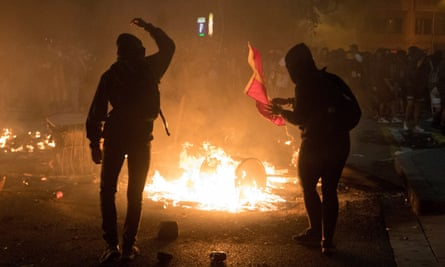 Protesters throw a Spanish flag into the flames