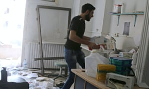 A man salvages medicine inside al-Quds hospital