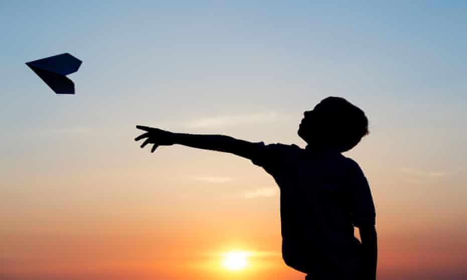 Boy throwing a paper aeroplane at sunset.