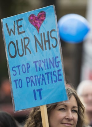 "A woman holds a ""We love our NHS"" placard."