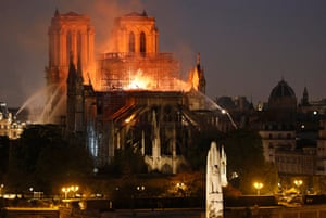 9:30pm: Firefighters douse the cathedral as flames and smoke are seen billowing from the roof.