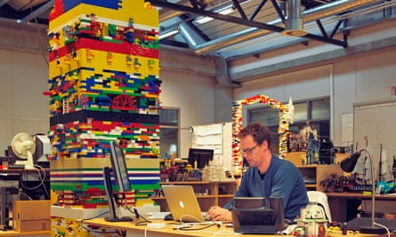 A man at a desk with a Lego tower next to the desk