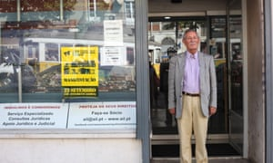 Romão Lavadinho, president of the Lisbon Tenants' Association, beside a poster advertising a housing protest.