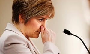 Nicola Sturgeon holding her nose while in front of a microphone, and looking anxious