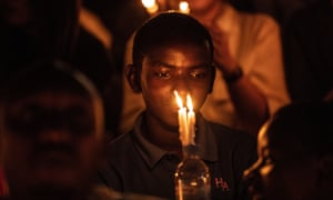 A boy holds a candle during a ceremony in Kigali in memory of the Rwandan genocide