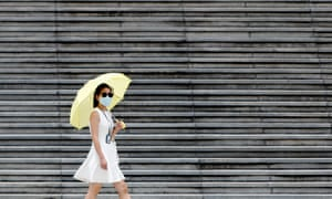 A woman wearing a face mask walks past at Liberty Square in Taipei, amid a domestic Covid-19 outbreak causing deaths and infections in Taiwan.