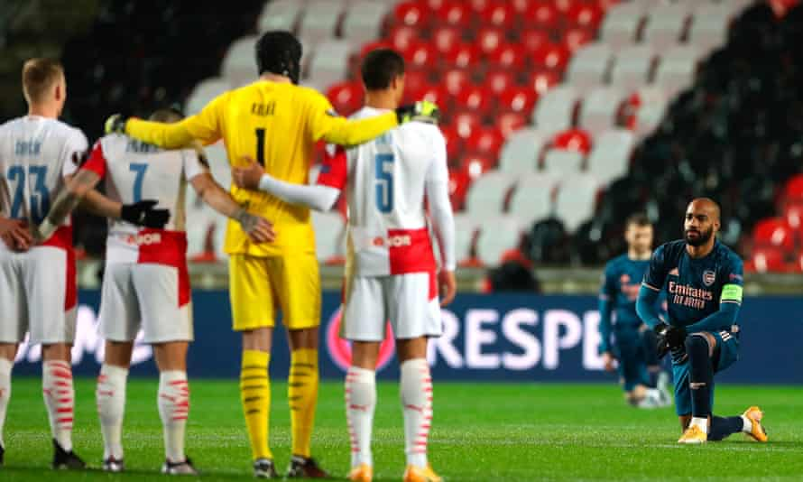 The Arsenal captain Alexandre Lacazette takes a knee in front of the Slavia players.
