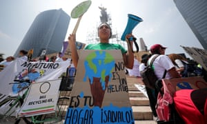 """A woman with a placard that reads in Spanish """"This is not an ice cream it is your home, take care of it."""""""