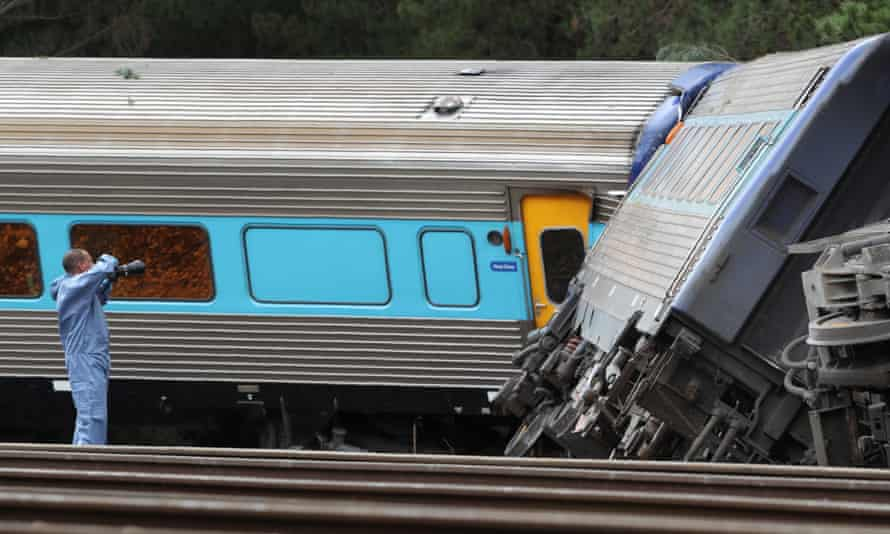 An investigator photographs carriages of the train that derailed near Wallan