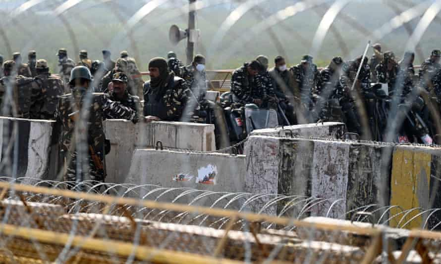 Indian security forces behind barbed wire and barracks.