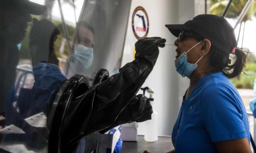 A nurse practitioner swabs the nose of a patient through a glass pane in Miami Beach, Florida.