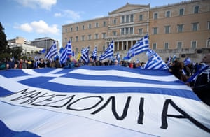 Protesters hold a giant Greek flag with the word Makedonia printed in large letters in front of the parliament building.