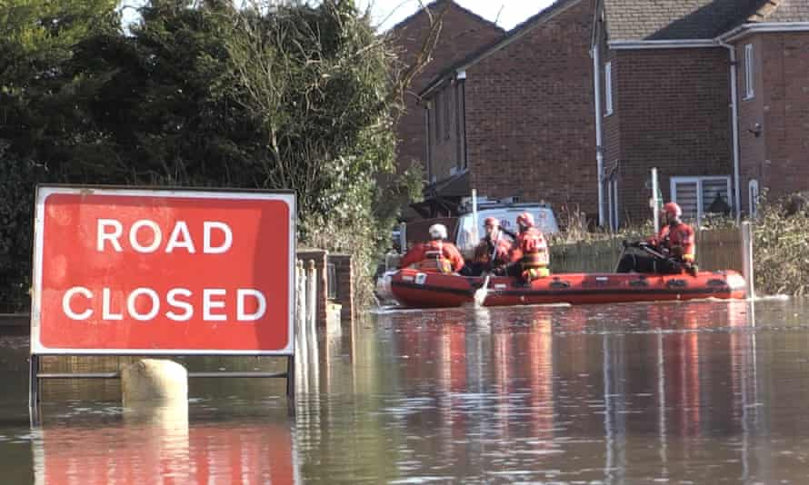 Firefighters use a dinghy to cross floodwater in Snaith, Yorkshire, on 27 February.