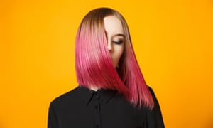 Girl with dyed hair waving headStudio shot of young colorful female on black blouse waving hair and isolated on orange.