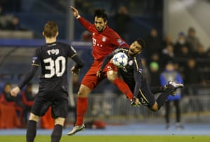 Bayern Munich's Medhi Benatia and El Arabi Hilal Soudani of Dinamo Zagreb, right, take to the skies in their battle for the ball.