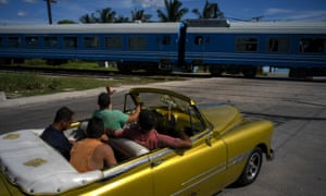 A driver in an American classic car waves as the first train using new equipment from China rides past, in Havana, July 2019.