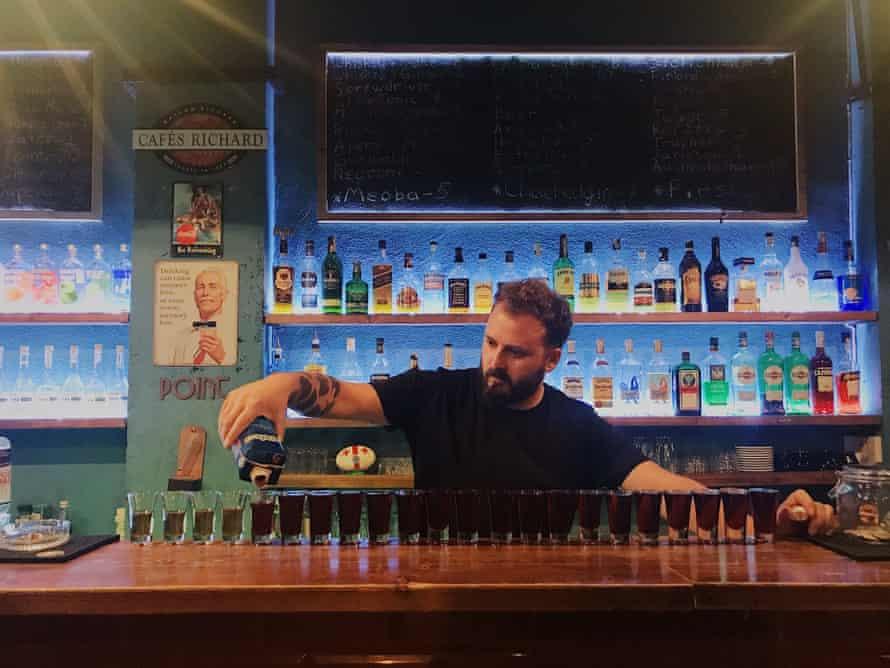 A barman pours drinks at Meoba bar