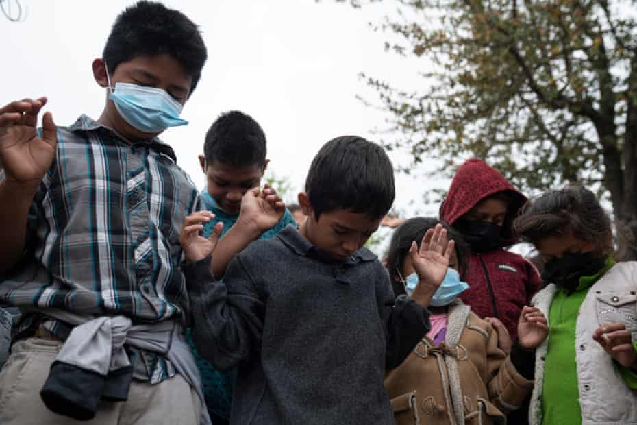 Asylum-seeking children pray in a plaza where some have been living for weeks after being sent back under Title 42 due to the pandemic with their parents in Reynosa, Mexico, on 24 March.