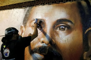 Street artist Badsura works on a portrait of Hernández on the main avenue in Chacao in Caracas