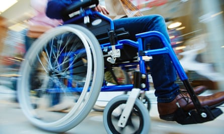 A man in a wheelchair being pushed
