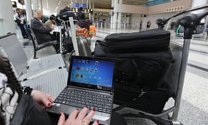 A woman travelling to the United States through Amman opens her laptop before checking in at Beirut international airport.