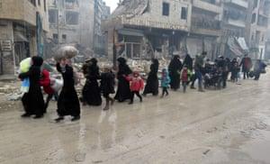 Syrian residents fleeing violence in the Bustan al-Qasr neighbourhood arrive in Aleppo's Fardos neighbourhood after regime troops retook the area from rebel fighters.