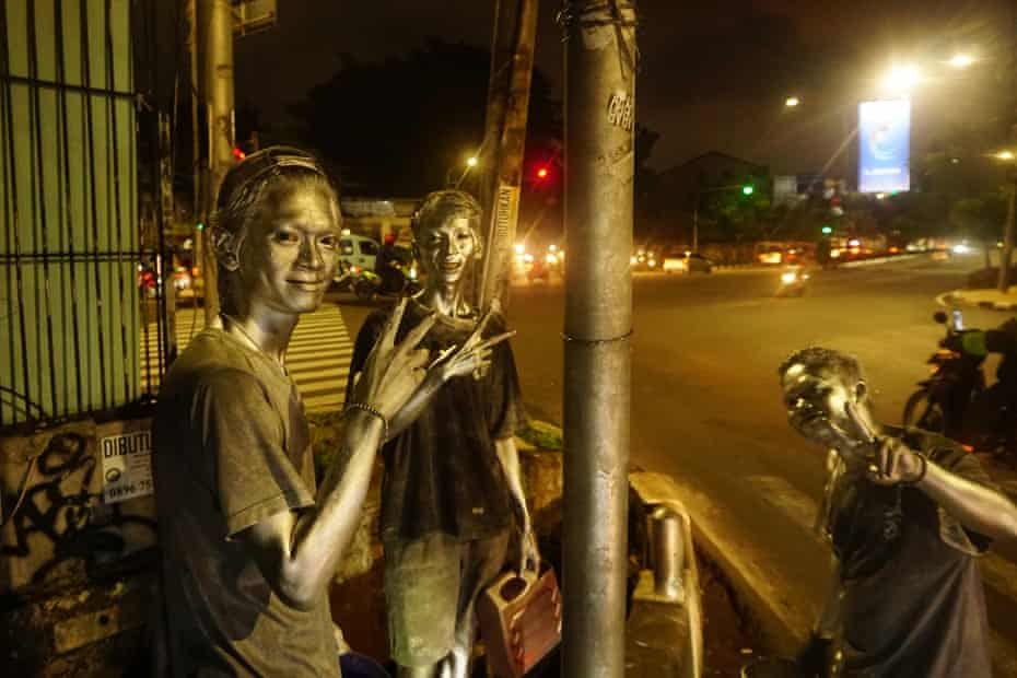 """Three boys with silver paint on their bodies, also known as """"Silverman"""" seen begging for money on a street in, Jakarta, Indonesia. Silver man, paint."""
