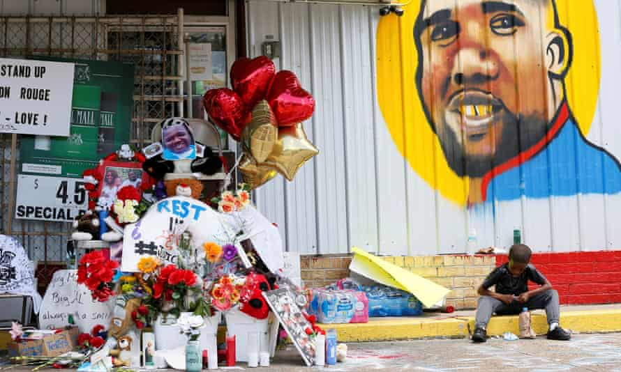 A boy sits next to a makeshift memorial outside the Triple S Food Mart where Alton Sterling was fatally shot by police in Baton Rouge, Louisiana.