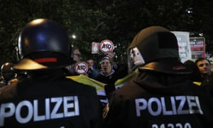 Protesters in Berlin hold placards and shout slogans against AfD after the election result.
