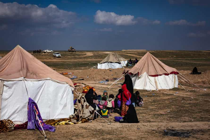 Women and children, believed to be Isis families, sit outside a tent at a civilian screening point while waiting for trucks to transport them to the al-Hoz refugee camp, on 9 February 2019