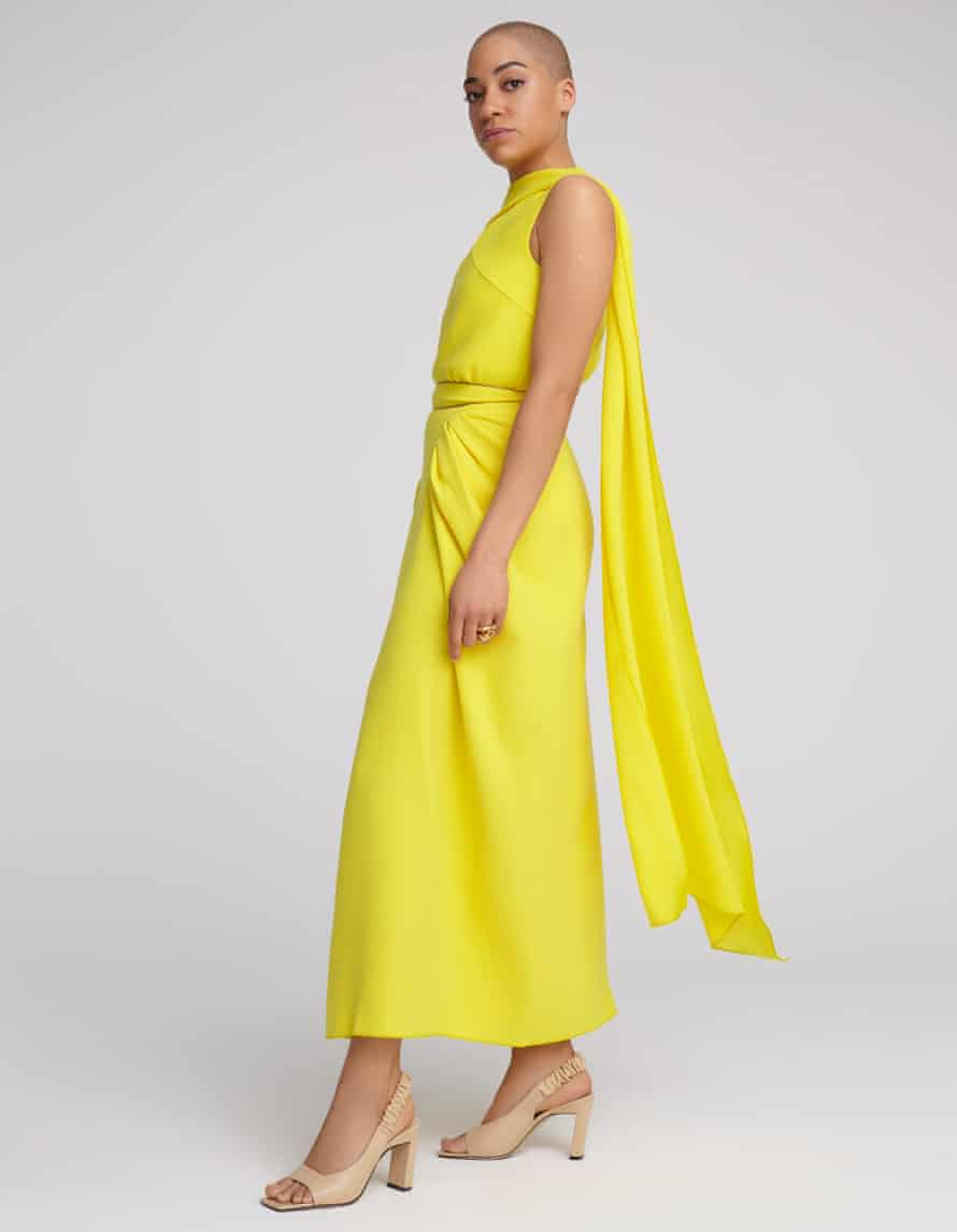 Actor Cush Jumbo in yellow top and skirt against grey background