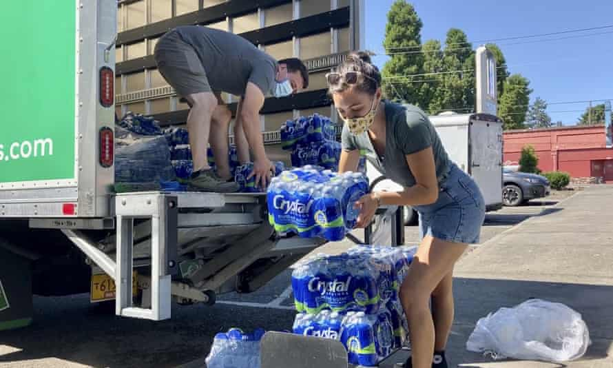 Volunteers and Multnomah county employees unload cases of water on Wednesday to supply a 24-hour cooling center set up in Portland.