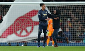 Manchester United defender Chris Smalling is shoved by a fan invading the pitch at Arsenal on Sunday.