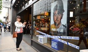 A Lush store with posters highlighting the misconduct of undercover police
