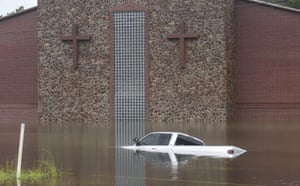 A truck sits largely submerged in floodwater in front of a church Thursday in Vidor, Texas.