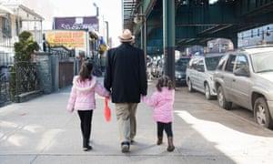 A man walks with children along Roosevelt Avenue in Queens