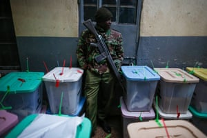 An armed police officer stands guard in the midst of a sea of ballot boxes at a tallying centre in the capital, Nairobi, Kenya
