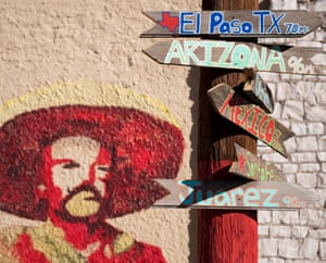 Signs telling the miles to different cities stands next to a mural of Mexican revolutionary leader Pancho Villa in Columbus, New Mexico