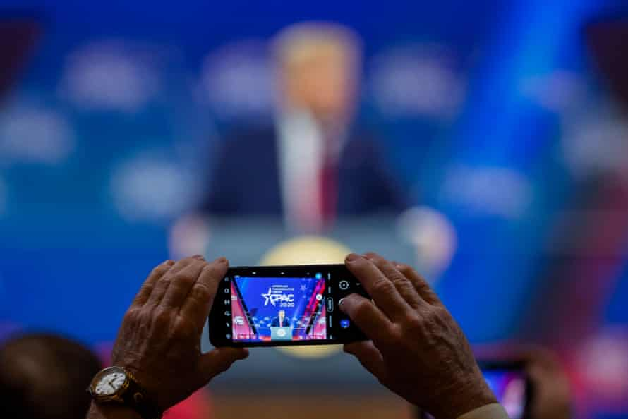A person takes a photo as Donald Trump speaks during CPAC in Maryland on 29 February 2020.