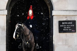 A member of the Household Cavalry on his horse on guard duty at Horseguards Parade as the snow falls in central London, Britain.
