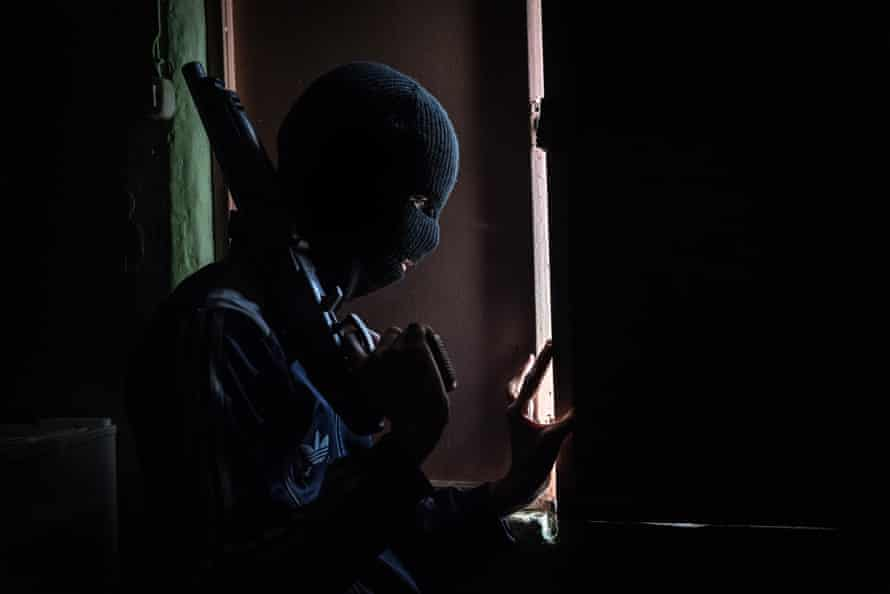 A member of a kidnapping gang watches through the window to avoid a potential police raid. He is 15 years old and joined the gang to support his family