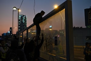 People help a man to climb a noise barrier to escape police following a pro-democracy march from the Tsim Sha Tsui district to Hung Hom in Hong Kong.