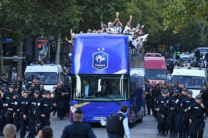 France's defender Raphael Varane (C) holds the trophy as he celebrates with teammates on the roof of a bus while parading down the Champs-Elysee avenue in Paris