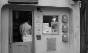 Black and white exterior of shop, with client's back seen through window of door of Mugi To Olive shop