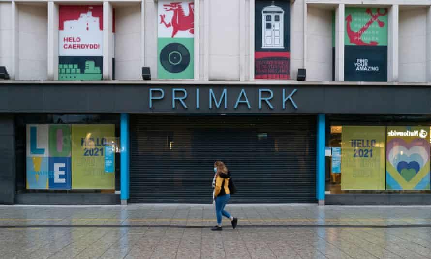 A woman walks past a closed Primark store in Cardiff.