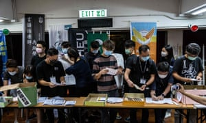 Masked people at a table counting votes from ballot boxes